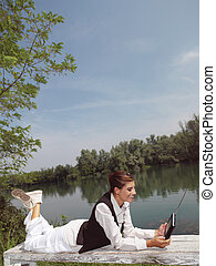 a woman with laptop in park okj