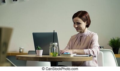 A woman with laptop sitting at the table in a cafe. - An...