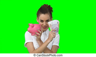 A woman with money and a piggy-bank in her hands