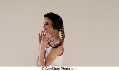a woman with pigtails listens to music with headphones and dancing