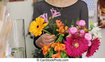 A woman working as a florist making bouquet in the store.
