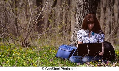 A woman working at a computer in the forest