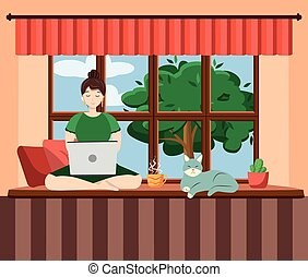 A woman works at a laptop while sitting on the windowsill at home. Freelance concept, quarantine due to covid-19.