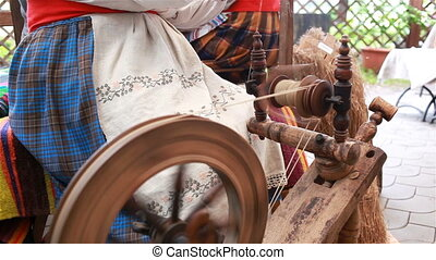 A woman works with a cloth on a spindle