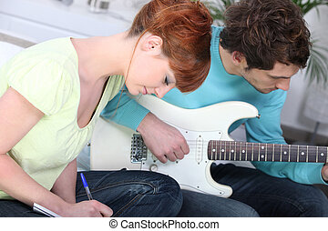 a woman writing and her boyfriend playing guitar