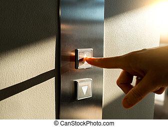 woman's finger presses the Elevator button