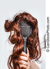 A woman's hand holds a comb with eyes and a wig that imitates a person's face. Hair care concept.