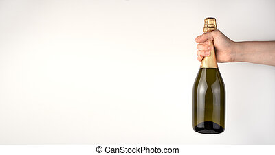 A woman's hand holds champagne on a light background.