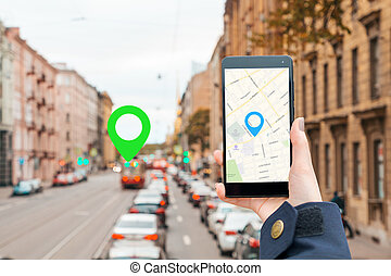 A woman's hand in a jacket holds a smartphone with an online map app. In the background is a blurred road with a traffic and icon of location.The concept of Internet navigation and modern technologies