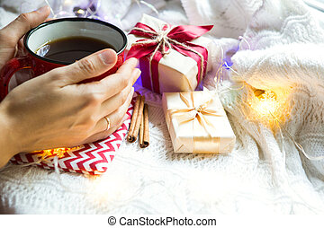 A woman's hand in a warm sweater holds a red mug with a hot drink on a table with Christmas decorations. New year's atmosphere, cinnamon sticks and a slice of dried orange, gifts, garland and tinsel