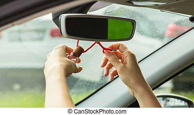 A woman's hand knots an air freshener on a mirror, close-up