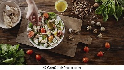 A woman's hand puts a mustard sauce at salad with natural...