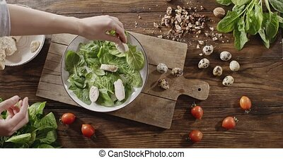 A woman's hand puts slices of chicken breast on a plate with shpinach. Top view of background with quail eggs, chicken fillet, greens, tomatoes, walnuts for cooking salad. Slow motion video in 4K.