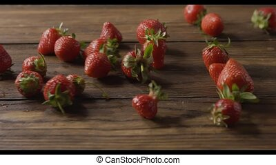 A woman's hand throws some red ripe wet strawberries, a handful of berries on a wooden table. Close-up tracking slow motion video. Full HD video, 240fps,1080p