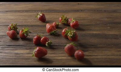 A woman's hand throws some red ripe wet strawberries, a...