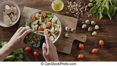 A woman's hands make photos mobile phone of salad from...