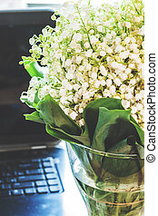 A woman's workplace, a bouquet of lilies of the valley in a vase near the laptop. With a retro vintage effect.
