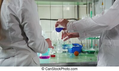 A women conduct chemical analyses in medical laboratory