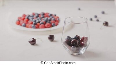 A women hand fills a glass with ripe red berries -...