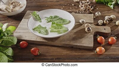 A women hand throws green spinach leaves on a white ceramic plate. The background with quail eggs, chicken fillet, greens, tomatoes, walnut for cooking salad on a wooden board. Slow motion video, 4K.