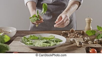 A women in apron throws spinach leaves on a white ceramic...