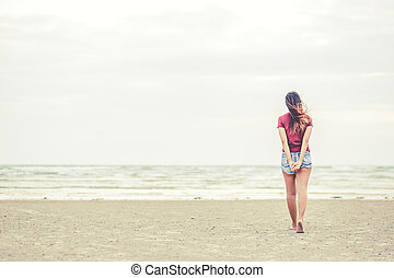 A women walking on the beach.