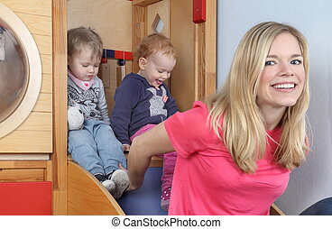 Women with kids in indoor playground - A Women with kids in...