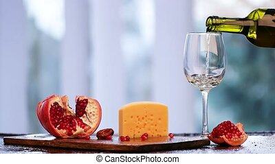 A wonderful cheese with a pomegranate and a glass of white wine sophistication