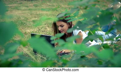 a wonderful lady lies in a park on the grass with laptop