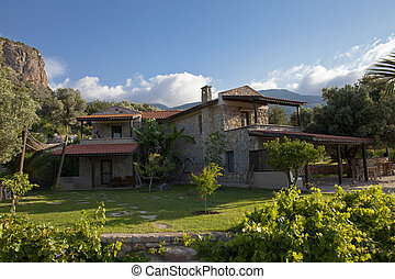 A wonderful stone house in green nature, Beautiful house view in the garden with blue sky and mountains.
