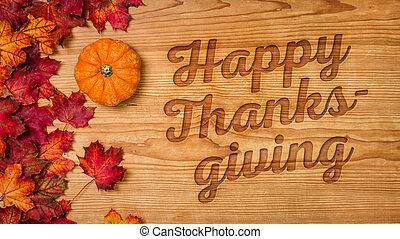 A wooden background with autumn foliage - Happy Thanksgiving