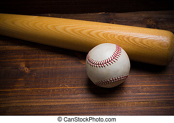 A wooden baseball bat and ball on a wooden background