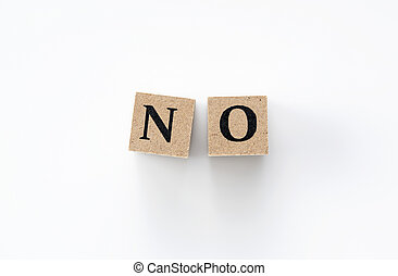 A wooden block with the word NO written on it on a white background