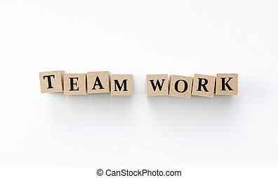 A wooden block with the word TEAM WORK written on it on a white background
