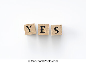 A wooden block with the word YES written on it on a white background