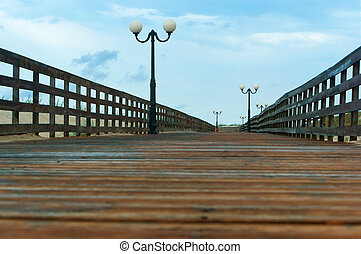 a wooden boardwalk with lights, wooden deck with railings