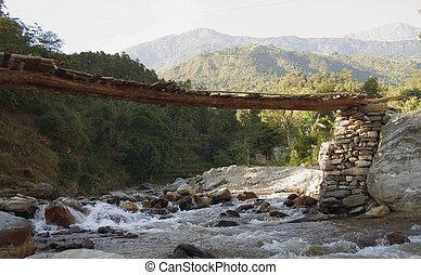 A wooden bridge over the mountain river
