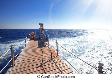 wooden bridge to the blue ocean ,sun is shining brightly in blue sky