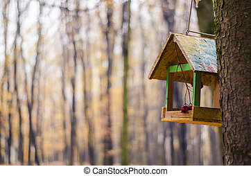 A wooden feeder on the background of a blurred forest.
