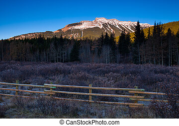 A wooden fence in a meadow in the Canadian Rocky Mountains