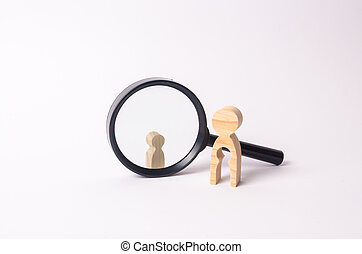 A wooden figure of a woman stands near the magnifying glass, behind which stands a child. The concept of finding a child, the adoption of children. Mother lost her baby and is now looking for him.