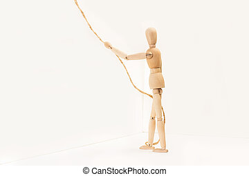 A wooden manequin toy holding holding a thin rope in his hand on a white background