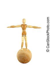 Wooden manikin standing on ball
