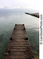 A wooden pier extends into a crystal clear alpine lake in Autumn, France