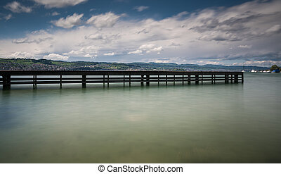 wooden pier on lake Zurich with rolling hills mountain landscape and sailboats in the background