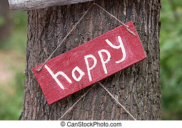 A wooden plaque with the word happy
