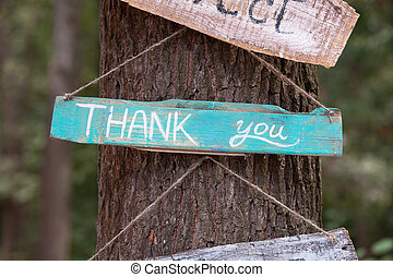 A wooden plaque with the word - thank you