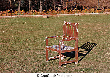 A wooden shabby chair stands on green grass