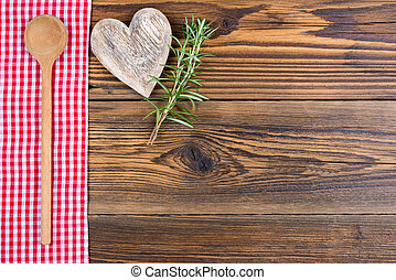 A wooden spoon, rosemary twigs and a heart of wood lie on a red and white chequered cloth on a rustic wood background with text space to design yourself.