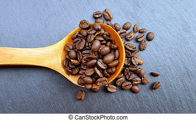 A wooden spoon with coffee beans